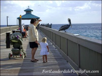 Father, daughter and pelican at the pier