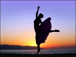 Woman dancing on the beach at sunset